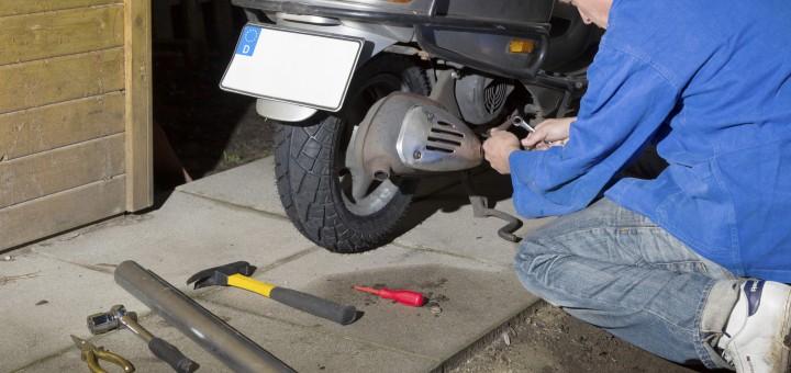 Mann montiert Hinterrad am Roller