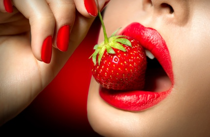 Sexy Woman Eating Strawberry. Sensual Red Lips